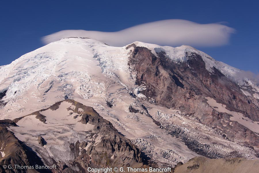 A lenticular cloud forms over the top of Mt Rainier. A landslide came down part of Willis Wall while I was watching. I heard the crack and saw dust rise as the debrey crashed down to the glacier below.