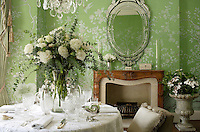 A Venetian-style glass mirror graces the chinoiserie de Gournay wallpaper above the fireplace in the dining room