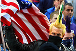 A punk swats away an American flag that blew too close to him during the May Day parade through downtown Portland.