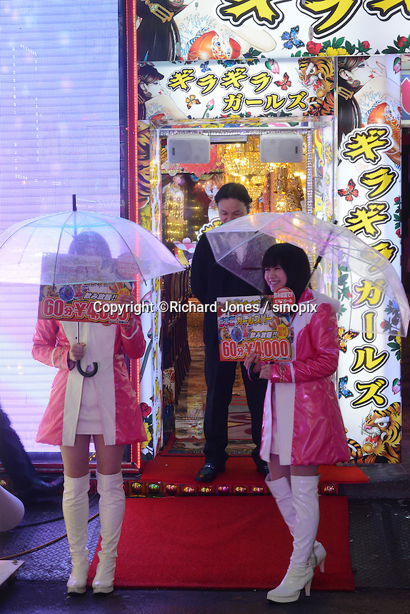 Two  young girls with umbrella are standing with Bikini Girls bar signs in rain. Glittery girls bar, 60 mins 4,000yen with unlimited drinks