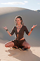 Yoga woman meditating in a pristine sand dune environment.