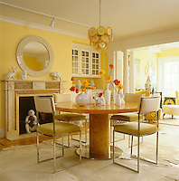 The dining room is suffused with warmth and light from yellow painted walls and the monkey hiding in the fireplace is one from of a large collection of the monkey-obsessed owner