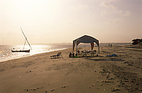 A dhow idles in the shallows off the beach while a gazebo, table and chairs have been set up in expectation of an evening meal