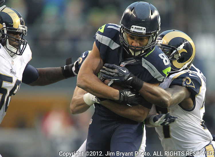 Seattle Seahawks Golden Tate is dragged down from behind by St. Louis Rams safety  Quintin Mikell, and linebacker Jo-Lonn DUnbar after catching an 18-yard pass from quarterback Russell Wilson at CenturyLink Field in Seattle, Washington on December 30, 2012.   Tate caught four passes for 105 yards in the Seahawks 20-13 come from behind win over the Rams.    © 2012. Jim Bryant Photo. All Rights Reserved.