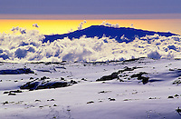 Clouds and snow at the summit of Mauna Kea. Hualalai mountain appears in the distance, set against bands of color in the late afternoon sun.