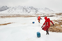 Kyrgyz girls slide large plastic jerry cans back to their family's camp after hacking a hole in the frozen river to fetch water. Men handle herding and trading; much of the hard labor of daily life falls to the women...The Kyrgyz settlement of Tchelab, near Chaqmaqtin lake, Haji Bootoo Boi's camp...Trekking through the high altitude plateau of the Little Pamir mountains, where the Afghan Kyrgyz community live all year, on the borders of China, Tajikistan and Pakistan.