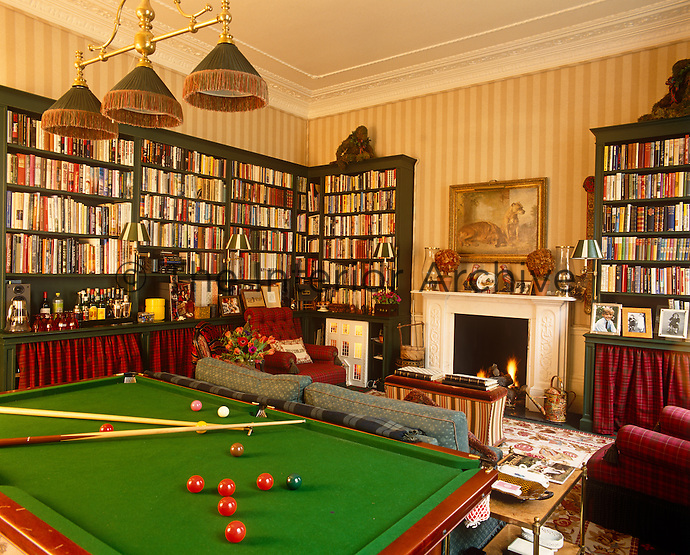 The bookcases lining this billiard room feature a lower storage area dressed in a tartan fabric to match the armchairs