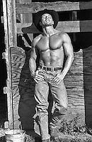 shirtless cowboy leaning on a barn door