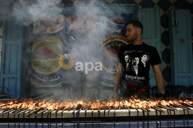 """A Palestinian vendor sells grilled meat """"Shish Taouk"""" in his shop at a market in Rafah in the southern Gaza Strip, on June, 04, 2012. Photo by Eyad Al Baba"""