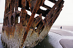 The wreck of the Peter Iredale Schooner at Fort Stevens State Park Clatsop County beach with young girl walking along the beach Northern Oregon Coast Astoria Oregon State USA