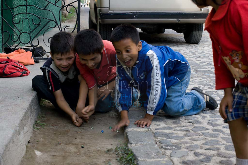 Young students play with marbles at Asociación Niño Obrero in Antigua, Guatemala. The non-governmental school is geared toward children and teens who could not attend public schools due to the challenged conditions in which they live. Tuition and the costs of uniforms and school materials can make public school prohibitive for poor families in Guatemala. Asociación Niño Obrero educates its students in both primary and technical curricula.