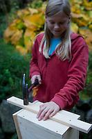 Mädchen baut einen Vogel-Nistkasten aus Brettern, 9. Schritt: Aufhängung anbringen