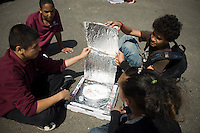 Students from the Urban Assembly's Academy of Civic Engagement Middle School cook s'mores in pizza box solar ovens in the Bronx on Monday, April 12, 2010.  The students constructed the solar ovens from pizza delivery boxes and after putting the s'mores in the ovens angled  the boxes toward the sun harnessing solar energy to cook the s'mores.  (© Frances M. Roberts)