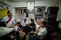 Activist have a meeting at the office of the National League for Democracy party decorated with pictures of Aung San Suu Kyi and her father general Aung San in Yangon March 29, 2012. Aung San Suu Kyi, the long-time standard-bearer for democracy in Myanmar, is taking a leap of faith in running for parliament on Sunday, opting to enter a political system crafted and run by the soldiers who kept her locked up for a total of 15 years. Her party's participation in this weekend's by-elections marks a change of heart for the Nobel Peace Prize winner who repeatedly rebuffed the military's attempts to bring her into a political apparatus in which it dictated the terms. REUTERS/Damir Sagolj (MYANMAR)