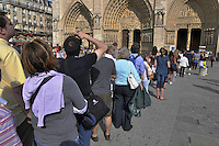 Tourists stand in line to the Notre Dame de Paris, France