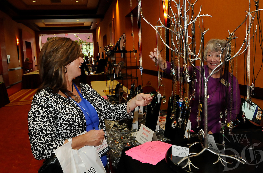 STAFF PHOTO FLIP PUTTHOFF <br /> CONFERENCE SHOPPING<br /> Deanna Ratcliffe, left, looks at jewelry made by Misty Baker, right, at Baker's booth on Tuesday Sept. 16 2014 at the Northwest Arkansas Business Women's Conference in Rogers.