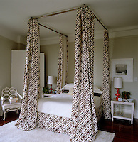 The bedroom is dominated by a large, contemporary four-poster bed with geometrically patterned curtains