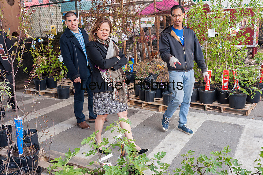"NYC City Council Speaker Melissa Mark-Viverto, center, with NYRP employee John Douglas, right, at the Urban Garden Center in East Harlem in New York on Sunday, April 27, 2014 at one of the New York Restoration Project's tree giveaways.The giveaway is part of the MillionTreesNYC initiative started in 2007 as part of the city's long term sustainability program. The goal is to increase the  ""urban forest"", comprised of street, park, public and private trees, to the betterment of the quality of life for New Yorkers.   (© Richard B. Levine)"