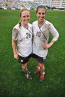 Rachel Buehler and Carli Lloyd pose in their mud stained uniforms after the US vs Norway game in Olhao, Portugal during the 2010 Algarve Cup.