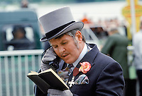 Well-dressed man using early mobile phone at Epsom Racecourse on Derby Day, UK in the 1980s