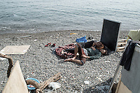 Syrian men sleep on the beach in daytime using the shade of a chalkboard barrier. Kos, Greece. Sept. 7, 2015