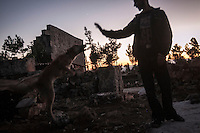 "In this Thursday, Sep. 26, 2013 photo, a Syrian displaced youth plays with his pet in the sunset at the Kafr Ruma, an ancient roman ruins used as temporary shelter by those families who have fled from the heavy fighting and shelling in the Idlib province countryside of Syria. Dozens of families settled in the ancient ruins known as ""The Forgotten City"" and declared human heritage by UNESCO, when the clashes between opposition fighters and government forces broke out in the region since more than two years ago. (AP Photo)"