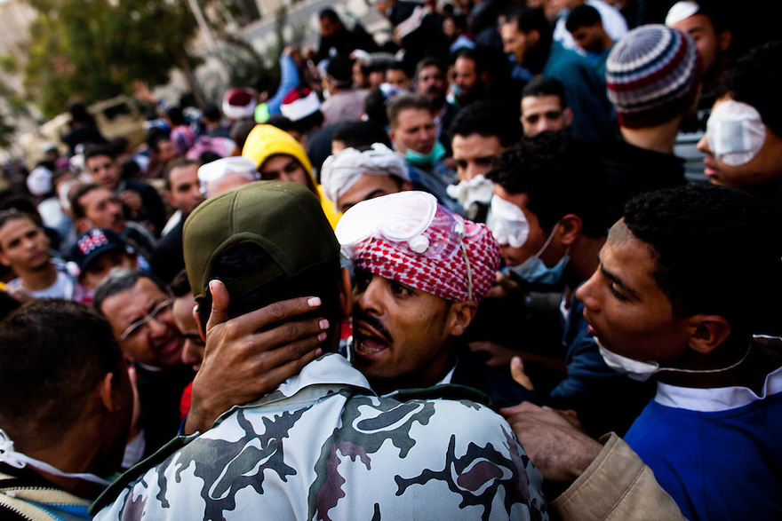 Protestors talk with a military officer on Mohamad Mohamad street during a truce between the police and the protestors brokered by religious leaders and the military. Street battles raged around the heavily fortified Interior Ministry, near Tahrir square, with police and army troops using tear gas and rubber bullets to keep the protesters from storming the ministry..The clashes have left at least 38 killed and 2,000 protesters wounded, mostly from gas inhalation or injuries caused by rubber bullets fired by the army and the police. The United Nations strongly condemned what it called the use of excessive force by security forces.