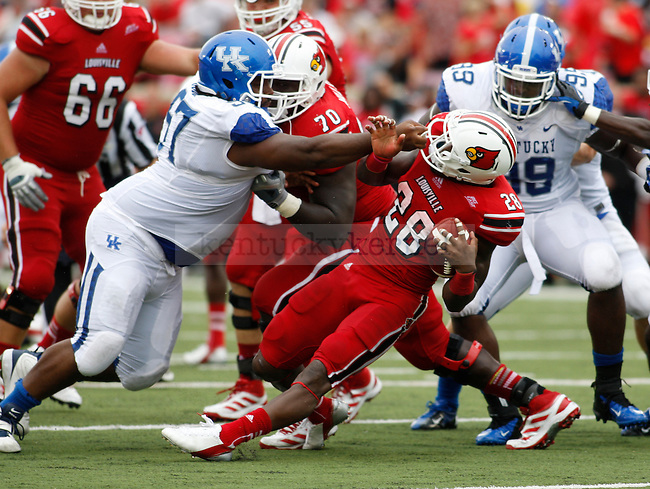 UL junior runningback Jeremy Wright gets tackled by UK players during the first half of the UK vs. UL football game at Papa John's Cardinal Stadium in Louisville, Ky., on Sunday, September 2, 2012. Photo by Tessa Lighty | Staff