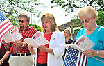 Claudia Borecky (center), newest member of the Merrick Historical Society Board of Trustees, reads the Declaration of Independence on July 4 with fellow board member Joe Baker (left), and visitor Marion Fraker-Gutin (right), at the Merrick Gazebo. =