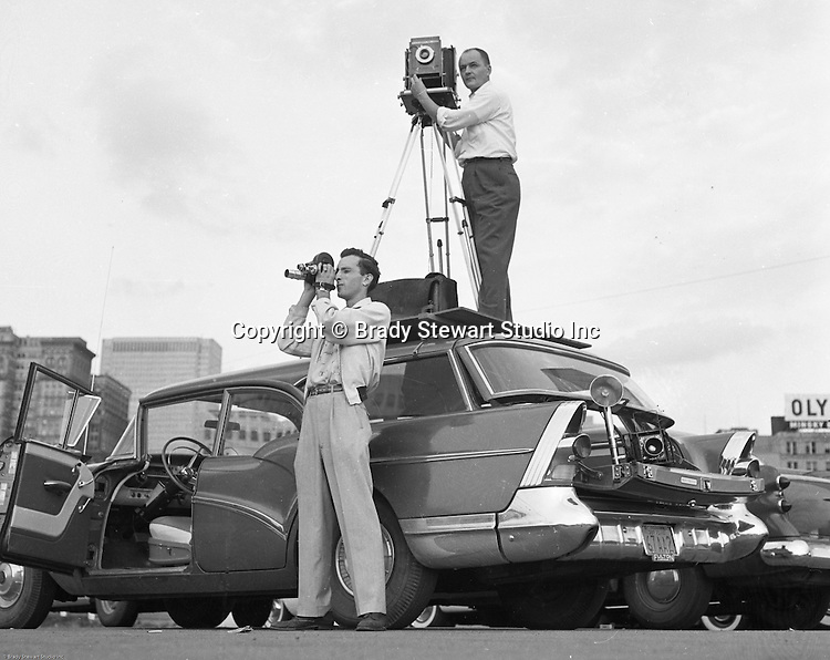 Pittsburgh PA:  Brady Stewart Studio on location for Morton Frozen Pies at Gateway Center in downtown Pittsburgh - 1957.  Assignment was for Ketchum McLeod and Grove Advertising. Brady Stewart Jr. and Ross Catanza handled the unique assignment.  View of Brady Stewart Jr. on top of the family's new 1957 Buick station wagon to get the right height for the shot and Jim Garvey shooting a 16mm film of the event.