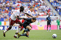 Adam Johnson (11) of Manchester City F. C. goes down under pressure from Tony Tchani (23) and Carlos Mendes (4) of the New York Red Bulls. The New York Red Bulls defeated Manchester City F. C.2-1 during a Barclays New York Challenge match at Red Bull Arena in Harrison, NJ, on July 25, 2010.