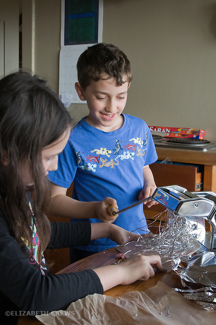Berkeley CASiblings, girl, 9, boy, 7, doing original experiment running foil through a pasta maker at home MR