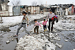 A Roma mother and her daughters walk through melting snow in a Roma settlement in Belgrade, Serbia, in February 2012. Roma living in Belgrade, often in miserable conditions, have faced increasing evictions from land they have claimed as their home.  The families that lived here, most of whom survive from recycling cardboard and other materials, were forcibly evicted in April 2012. Many were moved into metal shipping containers on the edge of Belgrade.
