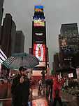 NYC, NY, USA. 19th Nov. 2015. Many people are in rainy Duffy Square in the heart of Times Square, the day after an ISIS propaganda video came out threatening New York City, particularly Times Square. Flags fly at half-mast. Coke, Gear S2, and other ads are on the tall electric billboard over the wet empty Red Steps. NYC's Mayor and Police Commissioner both said there is no specific and credible threat against New York City.