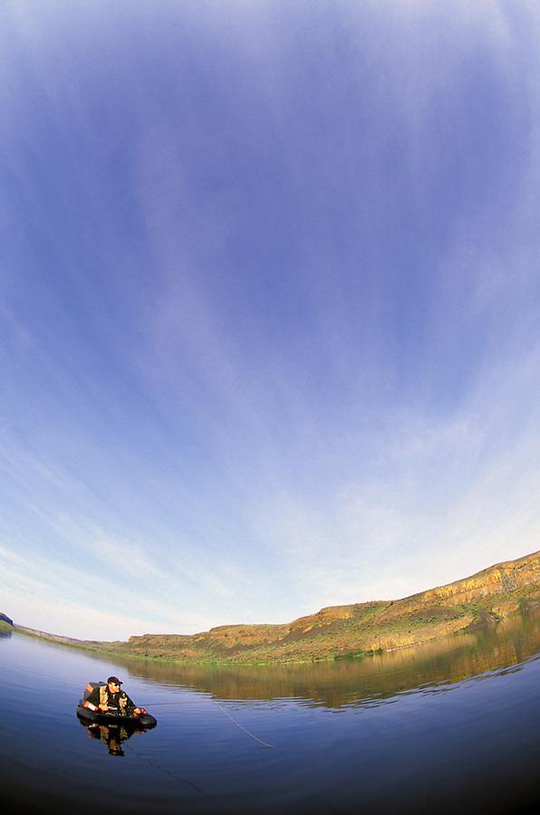 Man fly fishing from float tube in a desert lake, Grimes Lake, eastern Washington, Washington