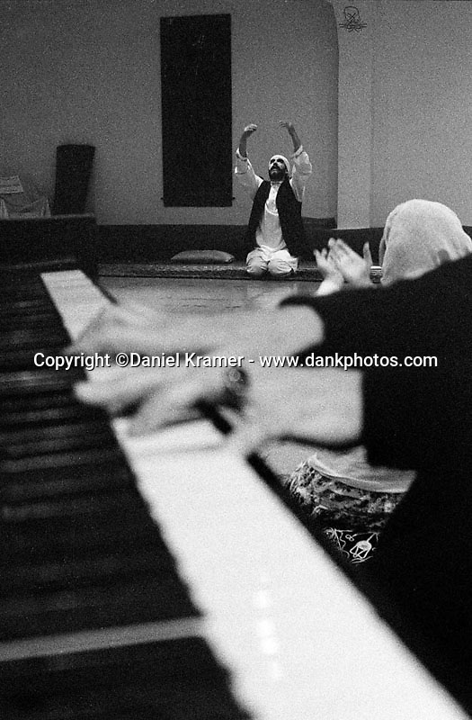 Sheik Loras and Ferishte Couglin raise their arms in prayer as Mariah Parker plays the piano. Music plays an integral part of the Whirling Dervishes search for spirituality.<br /> The Whirling Dervishes trace their origin to the 13th century Ottoman Empire. The Dervishes, also known as the Mevlevi Order, are Sufis, a spiritual offshoot of Islam. In 1972, Jelaluddin Loras, Sheik of the Mevlevi Order of America, brought the religion from Turkey to the United States. On December 17, Whirling Dervishes across the world celebrate the birth of Jelaluddin Mevlana Rumi, a mystic poet, who founded the Mevlevi Order. I am the first photographer allowed to document this group.