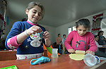 """Girls play with modeling clay in a church-sponsored """"child-friendly space"""" in the village of Bakhtme, Iraq, which was flooded with displaced families when the Islamic State group took over nearby portions of the Nineveh Plains in 2014. The space is sponsored by the Christian Aid Program Nohadra - Iraq (CAPNI). It includes some children from the host community as well."""