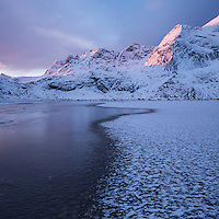 Winter sunrise over snow covered mountain peaks rising above frozen sand of Bunes beach, Moskenesøy, Lofoten Islands, Norway