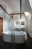 A large contemporary freestanding bath takes centre stage in the bathroom