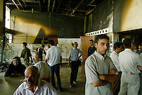 """Baghdad, Iraq, June 8, 2003.The public waits in the foyer of the looted Rasheed Theatre for the beginning of """"Obey the Devil"""" a dance show by the Mardohk Dance Group, a free adaptation of Shakespeare's Othello. Unfortunately one of Baghdad's power cuts forced the organiser to postpone the show for 4 days..."""