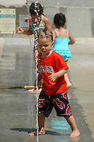 Children cool off in the water park at Douglas Park on Friday, June 22, 2007.