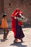 Indian woman with her child carries horse manure pats to dry for cooking fuel in Khore village, Rajasthan, Northern India