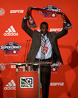 Tony Tchani of the University of Virginia raises his new team's scarf after being the  second overall pick of  the MLS Superdraft by the New York Red Bulls at the Pennsylvania Convention Center in Philadelphia, PA.