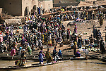 The Niger Riverbank in the village of Kouakourou fills with merchants and buyers each week on Saturday market day. Soumana Natomo, a grain trader (far back, at top, in blue) stands in front of his grain storage room. He and his two wives will haul grain out to sell. From coverage of revisit to Material World Project Natomo family in Mali, 2001.