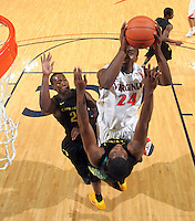 Dec. 17, 2010; Charlottesville, VA, USA; Virginia Cavaliers guard K.T. Harrell (24) is defended by Oregon Ducks forward Joevan Catron (34) and Oregon Ducks guard Teondre Williams (22) as he shoots the ball  during the game at the John Paul Jones Arena. Virginia won 63-48. Mandatory Credit: Andrew Shurtleff-