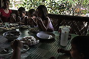 Ernesto Betasolo's daughter Rene Masung (left) sits down with the children for lunch in the kitchen of their house in Relocation Golden Valley in Barangay Pagkakaisa outside of Puerto Princesa, Palawan in the Philippines. <br /> Photo: Sanjit Das/Panos for Greenpeace
