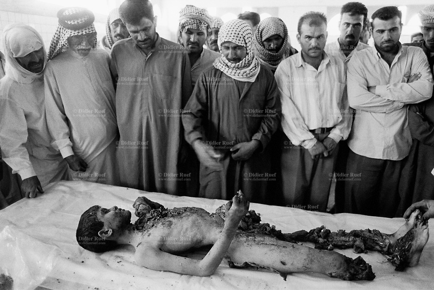 Iraq. Najaf. Morgue. A dead young boy who played with a left over shell which exploded and killed him. His father cries while the family relatives attend the bathing of the dead body. © 2003 Didier Ruef