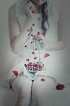 faceless portrait of a girl holding a white metal cage with red flowers in it and falling petals