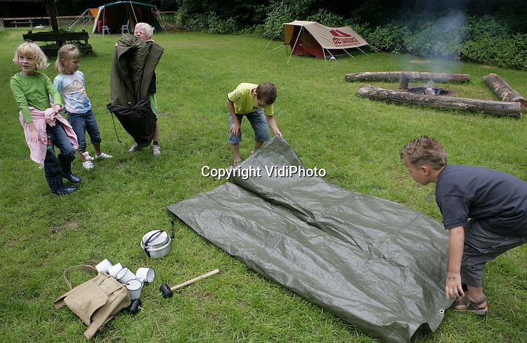 Foto: VidiPhoto..ARNHEM - Kinderen van 6-12 jaar kunnen deze zomervakantie in het Nederlands Openluchtmuseum in Arnhem leren kamperen op de ouderwetse manier. In de jaren 70 werd het kampeerpaspoort van de ANWB afgeschaft. Dat paspoort stond voor netheid, behulpzaamheid en etiquette. Kinderen krijgen nu de fijne kneepjes van het volleerd kamperen opnieuw bijgebracht, met als beloning een kampeerpaspoort na afloop van de cursus.