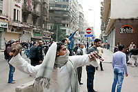 Protesters throw rocks at police on a street in central Cairo. Continued anti-government protests take place in Cairo calling for President Mubarak to stand down. After dissolving the government, Mubarak still refuses to step down from power.